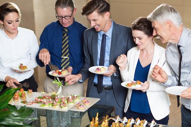 Executivos escolhendo snacks na mesa buffet
