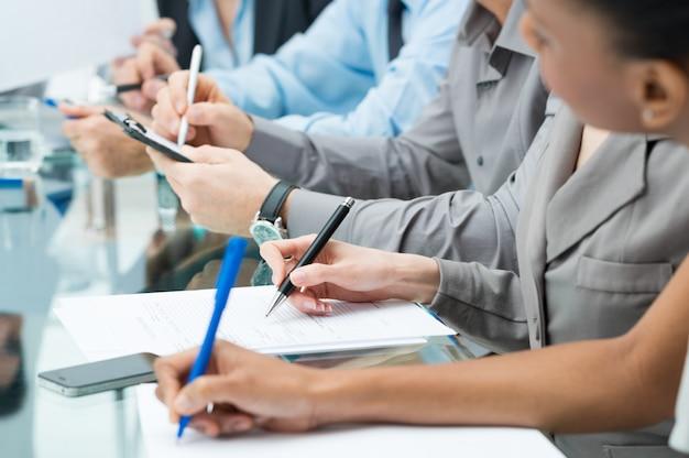 Executivos escrevendo nota na reunião