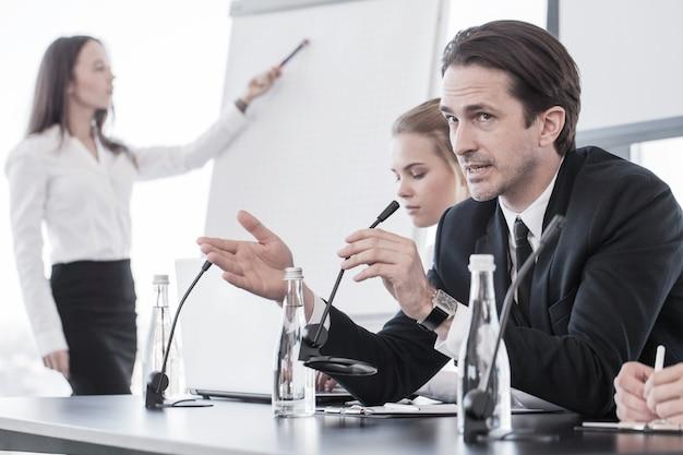 Executivos falando em uma apresentação no microfone no escritório