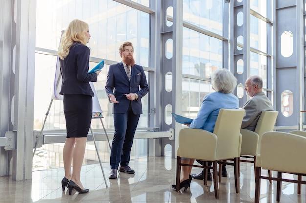 Executivos fazendo apresentações para o casal sênior no centro de negócios, investimento, conceito de investimento