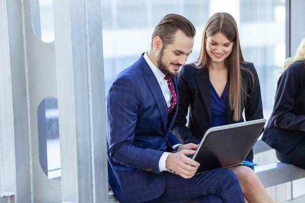 Executivos fazendo uma pausa, sentados com um laptop e sorrindo