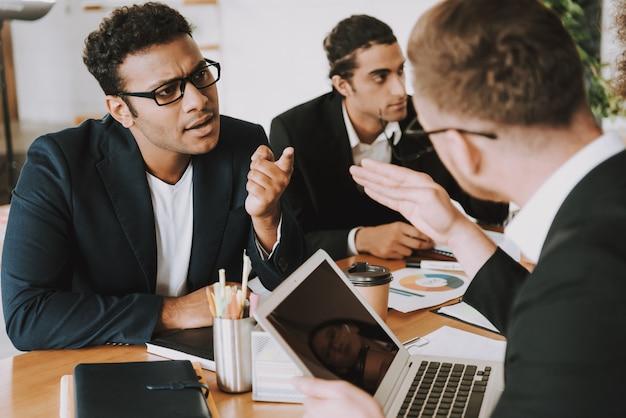 Executivos inter-raciais na reunião no gabinete.