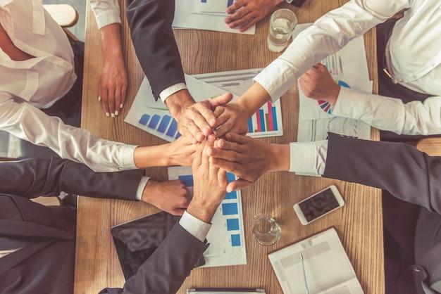 Executivos no vestuário formal que mantem as mãos unidas.