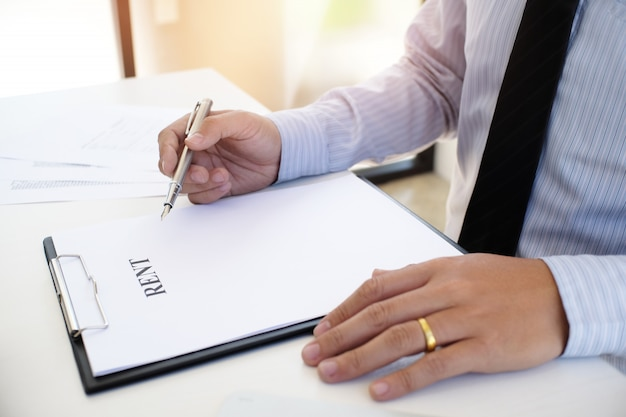 Executivos que assinam o contrato que faz um acordo com o mediador imobiliário conceito para o consultor e o conceito do seguro home.