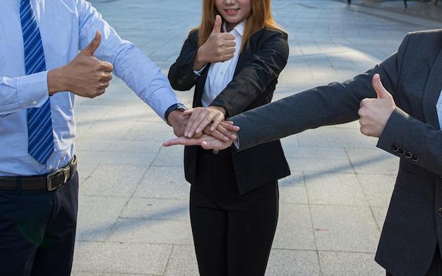 Executivos que dão o polegar acima e empilham as mãos junto no trabalho em equipe.