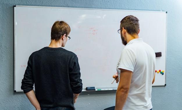 Executivos que encontram-se no escritório e usam notas de post-it para compartilhar a ideia.