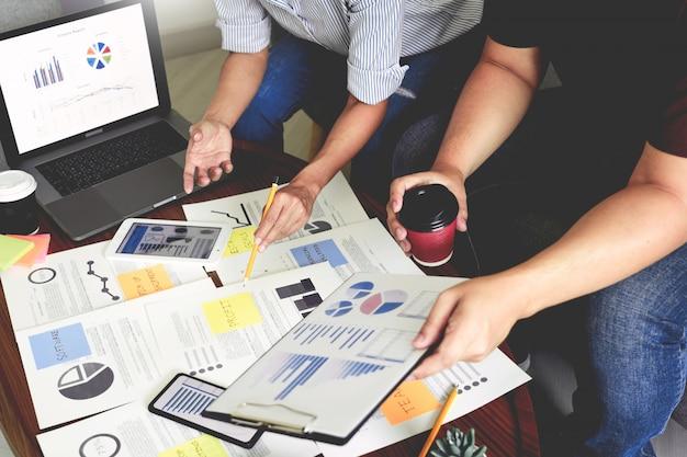 Executivos que escrevem em notas pegajosas para os colegas que pensam o plano de negócios da estratégia ou sobre o problema no escritório de coworking, conceito diverso da reunião de negócios do clique.