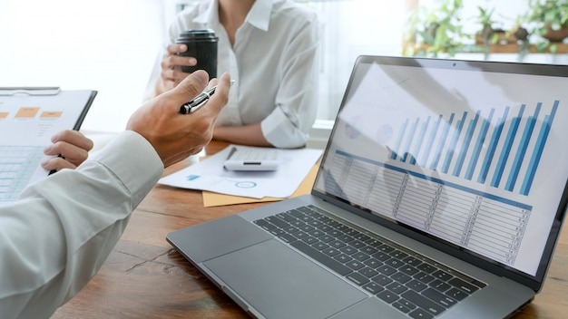 Executivos que falam discutindo com o colega de trabalho que planeja analisar tabelas e gráficos dos dados do documento financeiro na reunião e no conceito bem sucedido dos trabalhos de equipa.