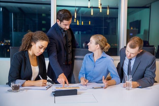 Executivos que falam em uma mesa de reunião