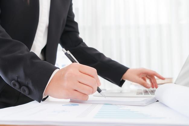 Executivos que usam um lápis anotando sobre o portátil