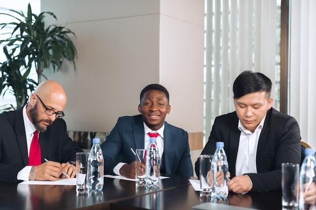 Executivos reunidos em torno de uma mesa de diretoria discutindo estratégias
