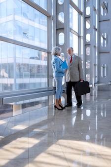 Executivos sênior conversando em um moderno centro de negócios