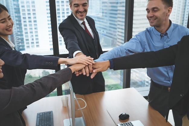 Executivos seniores da equipe de negócios e jovens funcionários juntam as mãos após reunião no escritório