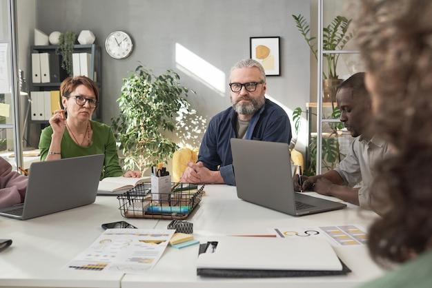 Executivos sentados à mesa com laptops e trabalhando em equipe em uma reunião de negócios