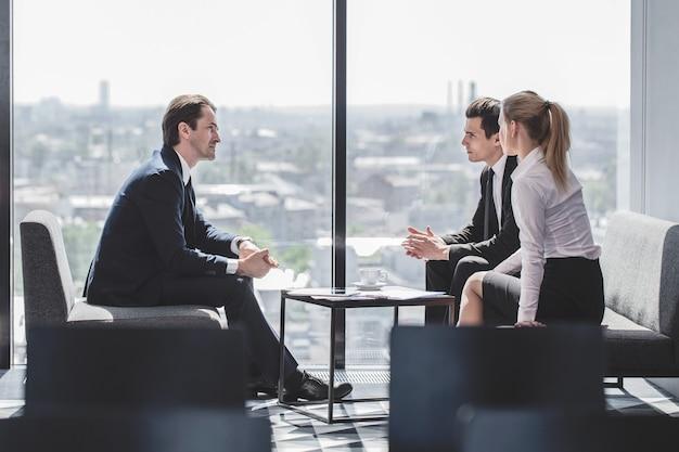 Executivos sentados perto de uma janela panorâmica com vista da cidade e conversando