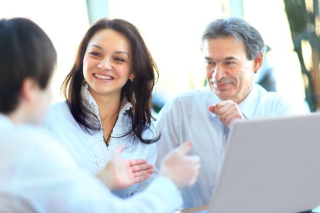 Executivos sorridentes com papelada na sala da diretoria