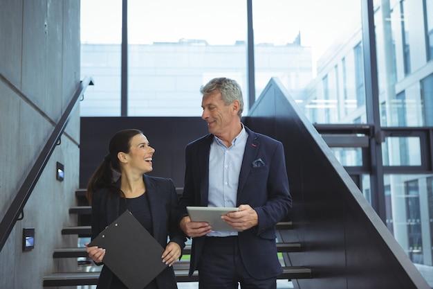 Executivos sorrindo enquanto se olham nas escadas