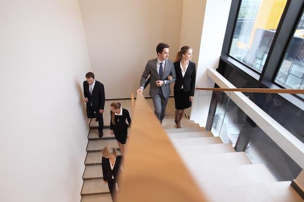 Executivos subindo escadas de edifício moderno