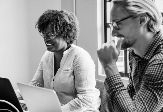 Executivos trabalhando em laptops durante uma reunião
