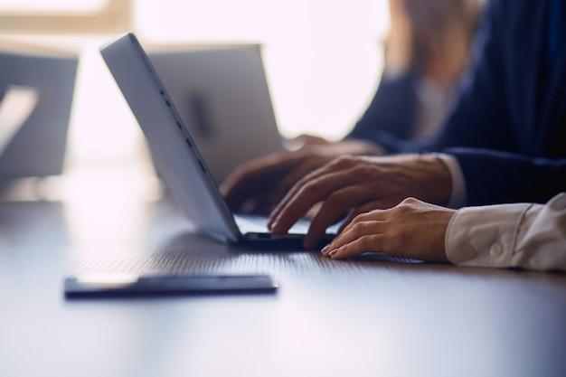 Executivos trabalhando no laptop. perto de mãos humanas. foco seletivo no braço feminino