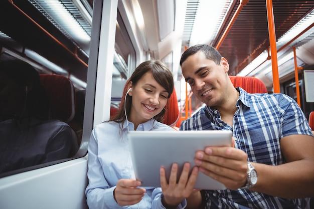 Executivos usando tablet digital viajando de trem