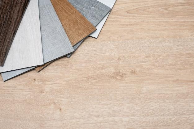 Exemplo de catálogo de pisos de vinil de luxo com um novo design de interiores para uma casa ou piso em uma mesa de madeira clara.