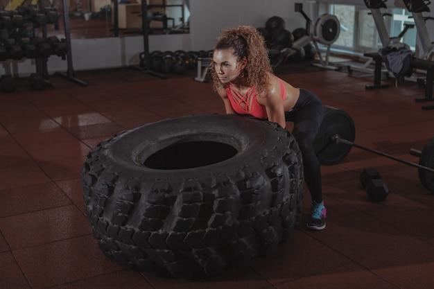 Exercício bonito da mulher do crossfit do ajuste