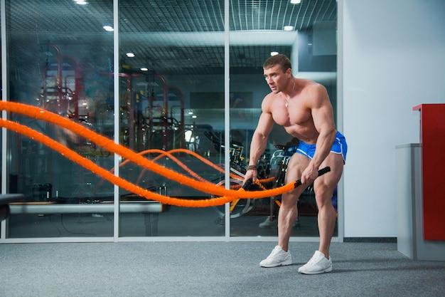 Exercício crossfit com corda, forte fisiculturista na academia