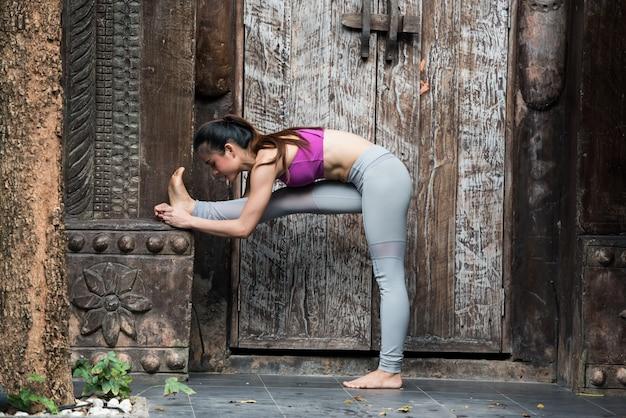 Exercício da jovem mulher do esporte com pose da ioga em casa.
