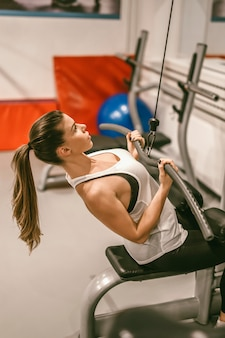 Exercício da jovem mulher na academia