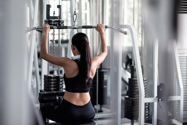 Exercício da mulher com a máquina de pulldown lat no ginásio