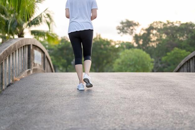 Exercício da mulher que anda no parque na manhã.