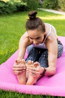 Exercício de alongamento. vista frontal de uma jovem se alongando em uma esteira de ioga