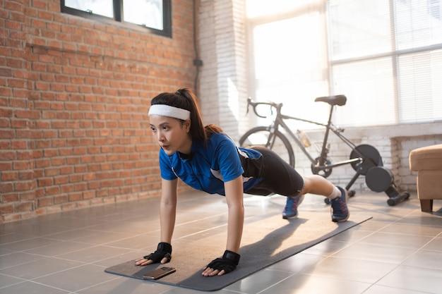 Exercício de ciclista com flexões. ela está em casa.