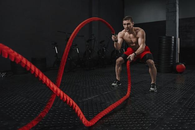 Exercício de crossfit com cordas de batalha durante o treinamento do atleta na academia