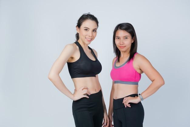 Exercício de duas meninas, menina do esporte em fundo branco, treino de mulher