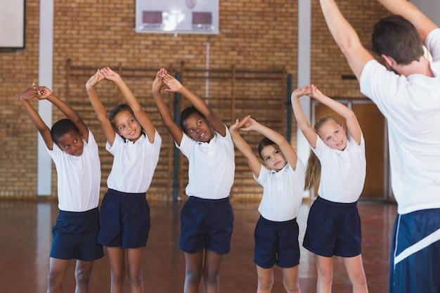 Exercício de ensino do professor para crianças em idade escolar na quadra de basquete