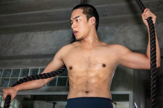 Exercício de escalada atlético da corda asiática do treinamento do homem no gym.