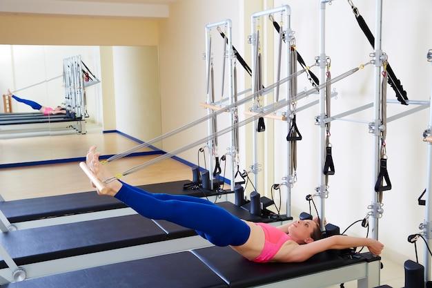 Exercício de espinha longa de mulher de reformador de pilates