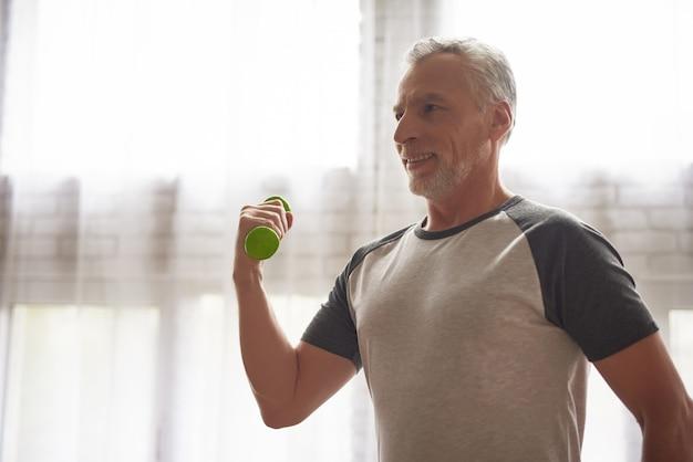 Exercício de fisioterapia de braços em casa para aposentados.