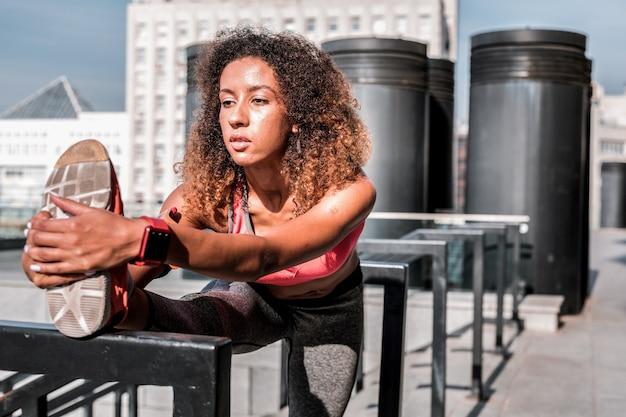 Exercício de flexibilidade. mulher séria e concentrada olhando para o pé enquanto faz um exercício de flexibilidade