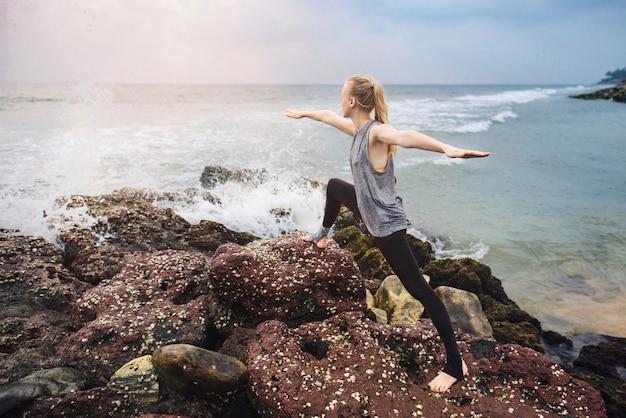 Exercício de ioga no penhasco do mar no pôr do sol