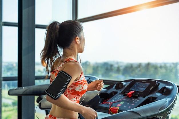 Exercício de jovem mulher com máquina de exercícios no ginásio.