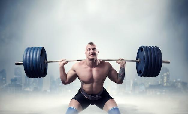Exercício de levantador de peso masculino musculoso com barra