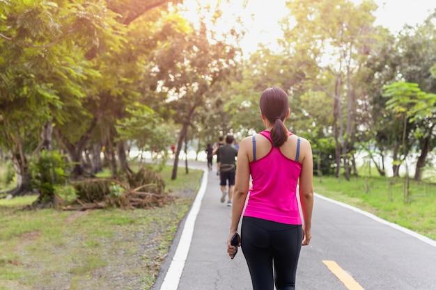 Exercício de mulher andando no parque com a mão segurando o telefone celular.