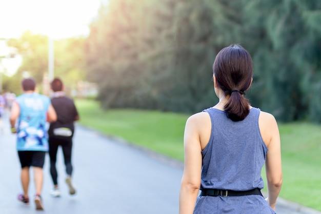 Exercício de mulher andando no parque de manhã