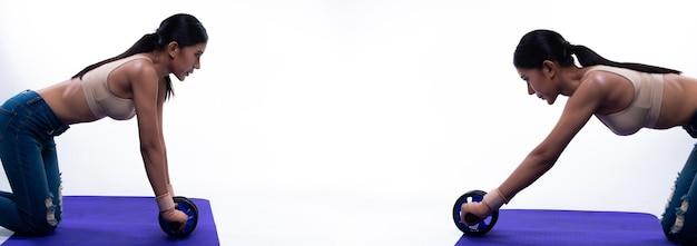 Exercício de mulher asiática slim fitness aquecer alongar o corpo muscular com o rolo de roda ab no tapete de ioga. senhora usa sutiã esportivo e calça jean, conceito que mulher pode praticar esportes saudáveis