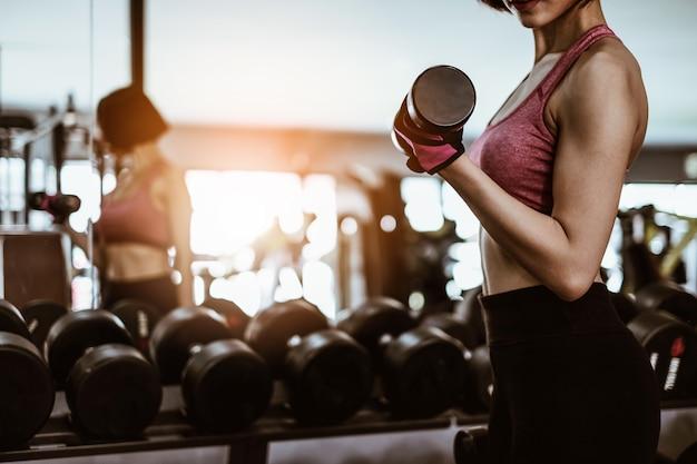 Exercício de mulher atraente ajuste com halteres em fitness ginásio