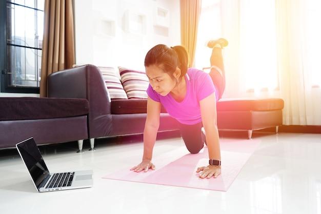 Exercício de mulheres asiáticas fazendo arqueamento volta endireitando perna até treino em casa