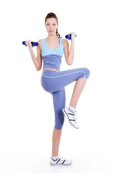 Exercício de treinamento físico de uma jovem mulher bonita com halteres